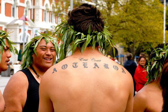 """Nuoria maorimiehhiä yhden selässä tatuoitu teksti """"Aotearoa""""."""