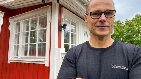 Hannu Tarkkio seisoo punaisen omakotitalon portailla. Hänen olan takaa näkyy kaksi valvontakameraa