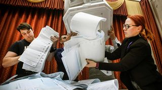 Vaalityöntekijät tyhjentävät vaaliuurnaa ääntenlaskua varten.