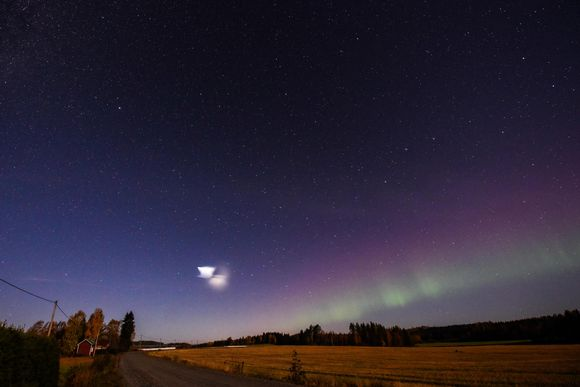 Raketista aiheutunut valoilmiö kuvattuna Nurmeksessa. Taustalla upeat revontulet yössä.