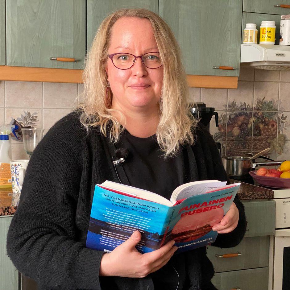 Tietokirjailija Jonna Pulkkinen keittiössä käsissään tuore teos Punainen pusero.