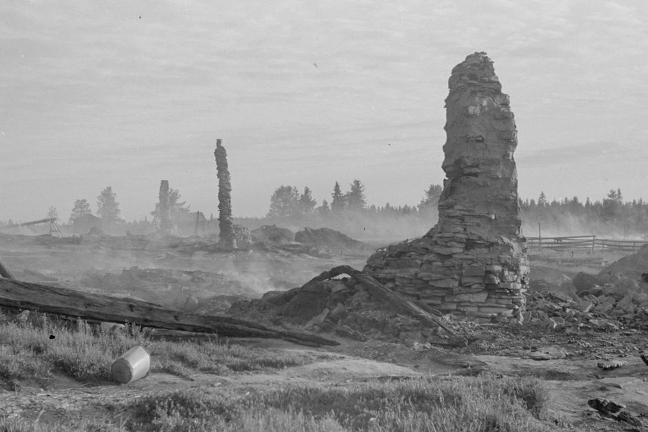 Mustavalkoinen kuva partisaanien tuhoamasta Lokan kylästä, savuavasta maasta törröttää savupiippujen raunioita.