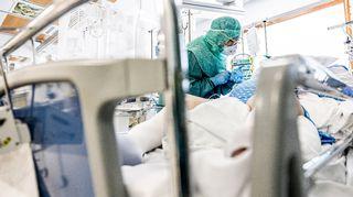 Sairaanhoitaja hoitaa koronapotilasta suojavarusteissa teho-osastolla