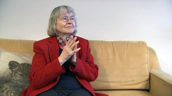 Liisa Kauppinen istumassa sohvalla.