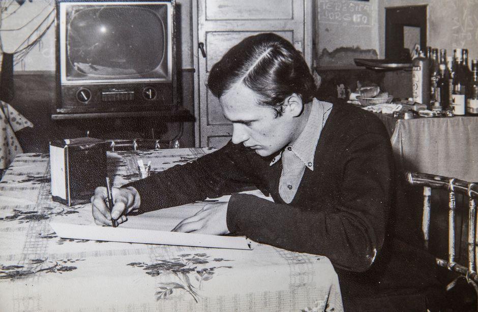 Mies kirjoittaa pöydän ääressä.